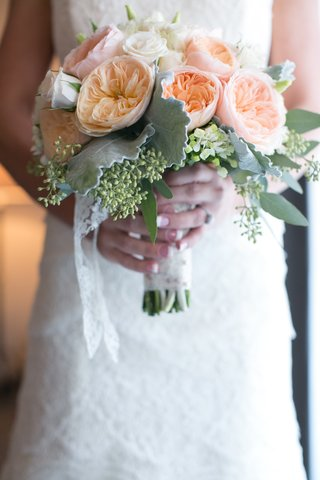 bride-holding-orange-garden-rose-and-white-rose-bouquet