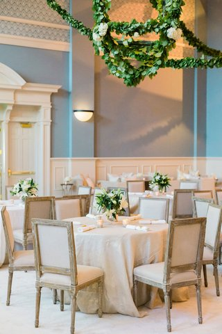 wedding-reception-blue-walls-garlands-greenery-on-lantern-chandelier-over-tables-with-beige-linens