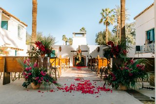 outdoor wedding ceremony at la quinta resort and club wood cross flower petals pews tropical greenery