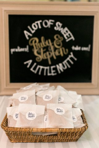 wedding-reception-table-of-praline-favors-in-white-bags-stickes-with-couples-names-in-a-wicker