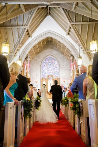 bride-holding-arm-of-father-of-bride-down-red-carpet-aisle-runner-church-ceremony-stained-glass