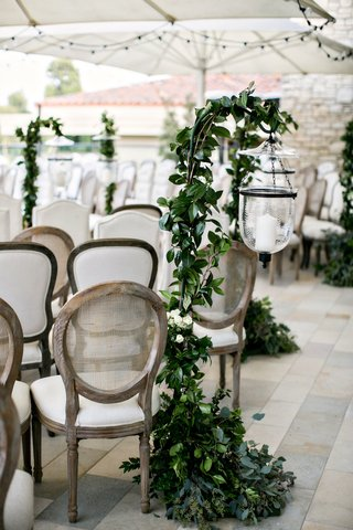 wedding ceremony stone tile umbrella lighting etched glass cane back chairs greenery