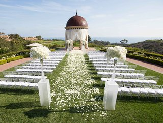 outdoor-ceremony-space-gold-course-ocean-white-chairs-flower-petals-dome-pelican-hill-resort-ca