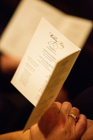 guest-holds-formal-wedding-ceremony-program