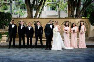wedding party groom and four groomsmen in tuxedos three bridesmaids in light pink dresses draped