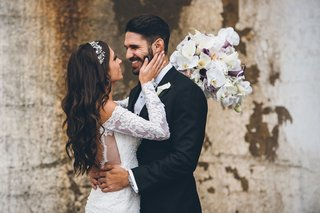 bride-in-off-shoulder-lace-wedding-dress-holds-grooms-face-after-first-look-wedding-photos
