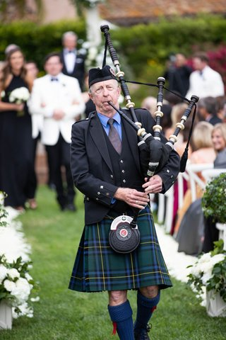 wedding ceremony outdoor lawn bagpipe player walking down aisle with bridesmaids groomsmen behind