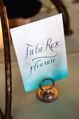 wedding-reception-table-sign-with-a-tiffany-blue-gradient-flower-name-and-meaning-in-calligraphy