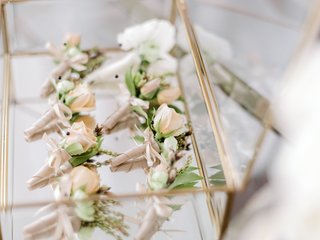 peach-boutonnieres-for-groom-and-groomsmen-in-glass-case-with-gold-trim