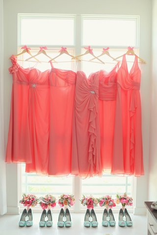 bridesmaid-dresses-in-different-styles-on-hangers-above-mint-heels-and-bouquets