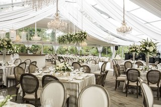tent-outdoor-space-chandeliers-champagne-hues-wedding-reception-hanging-greenery-tan-linens