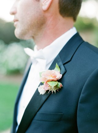 groom-in-tuxedo-jacket-with-white-bow-tie-and-unique-boutonniere-unique-flowers