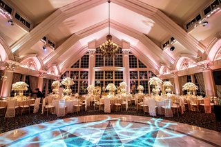 oval-dance-floor-with-blue-lighting-chandelier-gold-and-white-centerpieces-at-ballroom-reception