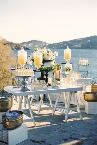 outdoor-wedding-ceremony-refreshment-station-lemonade-and-water-gold-ice-bucket-mason-jars-straws