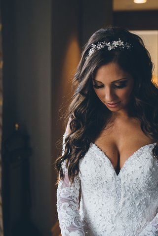 bride-in-low-cut-lace-wedding-dress-embellished-long-sleeves-headpiece-long-brown-hair