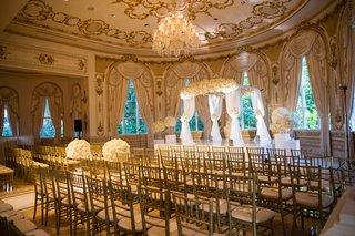 wedding-ceremony-indoor-ballroom-chandelier-white-flowers-ceremony-arch