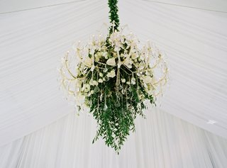 crystal-chandelier-accented-with-greenery-and-ivory-roses-at-tented-wedding-reception
