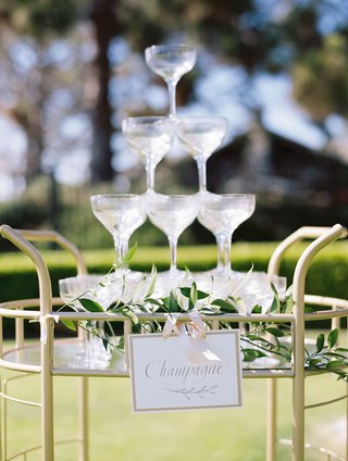 wedding-reception-cocktail-hour-champagne-in-coupe-glasses-flutes-served-in-tower-on-gold-bar-cart