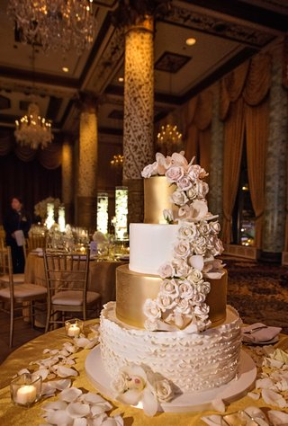 white-gold-and-blush-four-tier-wedding-cake-with-cascading-flowers-on-gold-table-linens