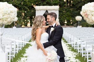 groom-in-lanvin-bride-in-reem-acra-embrace-look-into-each-others-eyes-classic-outdoor-ceremony