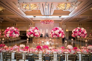 wedding-reception-ballroom-pink-flowers-gold-chairs-large-dance-floor-ballroom-chandelier