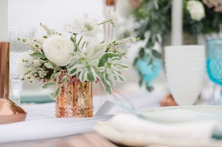 small-rose-gold-stand-with-white-and-green-floral-arrangement-on-blue-and-white-tablescape
