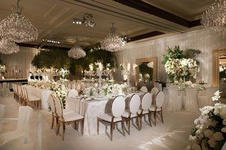 wedding-reception-white-linen-metallic-chairs-chandeliers-greenery-gold-mirrors-ballroom-reception