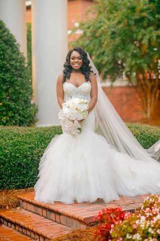 bride-with-long-curled-hair-mermaid-wedding-dress-sweetheart-neckline-orchid-bouquet-cathedral-veil
