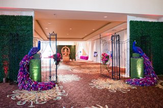 indian-wedding-gate-framed-by-peacocks-made-from-flowers-and-greenery-wall