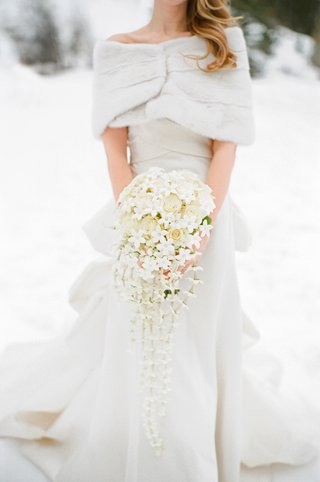 bride-in-wintry-wedding-dress-holding-flowers