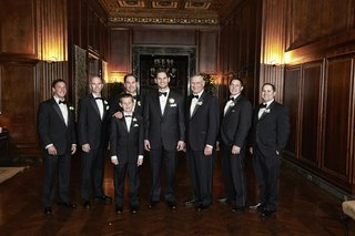 men-in-black-tuxedos-and-bow-ties-in-wood-room