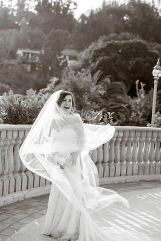 black-and-white-photo-of-twirling-bride-smiling-bouquet-balcony-bel-air-bay-club-california