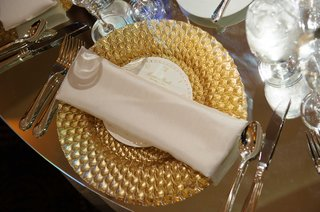 an-intricate-gold-charger-plate-topped-with-a-white-napkin-on-a-gilt-table-top
