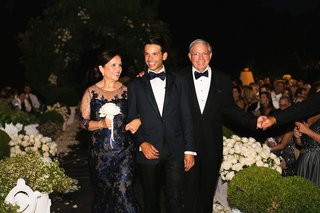 groom-in-suit-with-bow-tie-and-parents-mother-of-groom-in-sheer-neckline-navy-blue-evening-gown