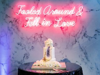 geode-wedding-cake-with-neon-sign-above-reading-folled-around-fell-in-love