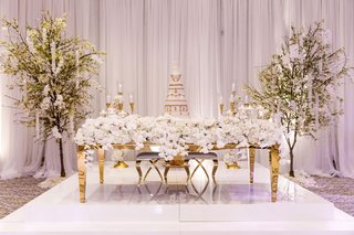 long-rectangular-gold-sweetheart-table-nfl-player-tahir-whitehead-cake-blossom-trees-white-stage