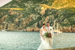 a-bride-and-groom-in-full-wedding-attire-in-front-of-the-pacific-ocean-in-cabo-san-lucas-mexico
