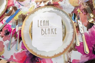white-and-gold-calligraphy-on-white-paper-white-china-gold-detailing-pink-floral-table-linen