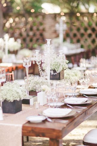 wood-table-with-sequin-runner-and-cube-boxes-of-white-flowers