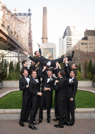 groomsmen-sporting-black-tuxedos-playfully-lift-the-groom-above-their-heads-in-nyc