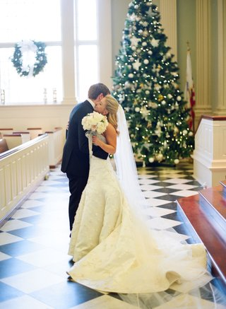 bride-and-groom-hug-in-front-of-christmas-tree