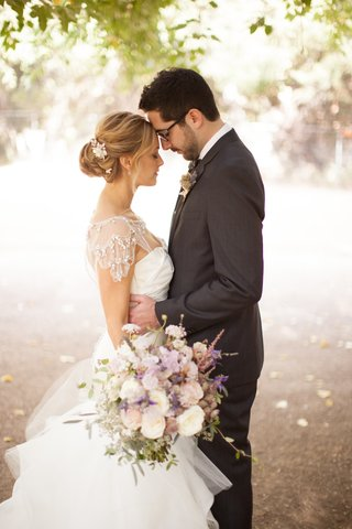 couple-in-wedding-attire-touching-foreheads
