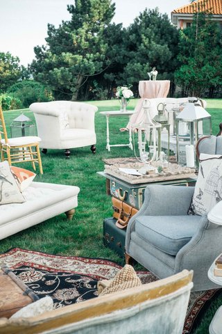 outdoor-lounge-space-with-white-and-blue-chairs-and-couches-area-rug-lamps-vintage-luggage