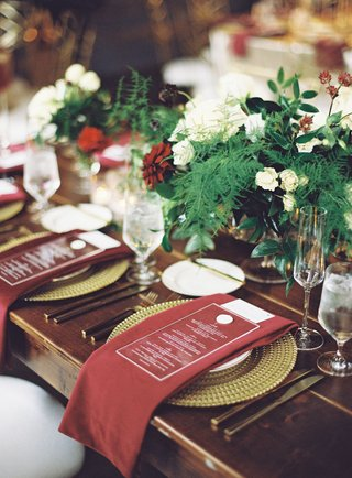wedding-reception-dark-wood-table-gold-plate-burgundy-red-napkin-acrylic-menu-greenery-centerpieces