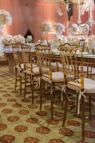 gold-amber-wedding-chairs-with-ivory-cushions-tied-around-mirror-long-rectangle-table