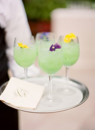wedding-signature-cocktail-in-white-wine-glass-with-light-green-drink-and-edible-flowers