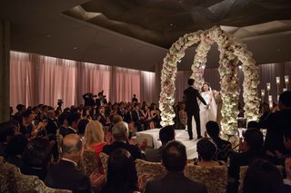 bride-and-groom-holding-hands-at-wedding-ceremony-in-ballroom-under-two-flower-arches-candlelit