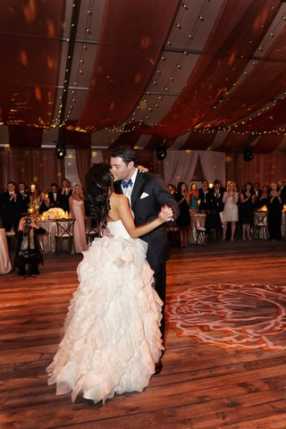bride-and-groom-kiss-during-first-dance-on-rustic-dance-floor