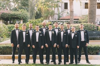 groom-with-10-groomsmen-in-matching-black-tuxedos-for-palm-beach-wedding