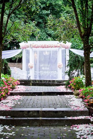 wedding-ceremony-bricks-with-white-pink-flower-petals-ceremony-arbor-pink-flowers-white-drapes